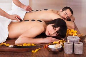 Beautiful Young Couple Enjoying Hot Stone Therapy