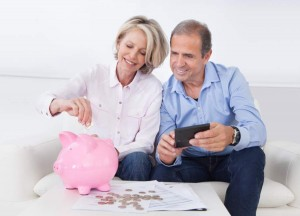 Mature Couple Calculating Coin In The Piggybank